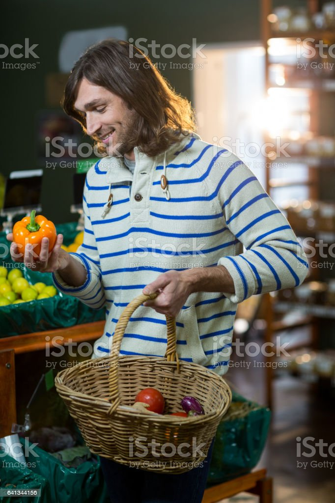 Man with a baskets selecting bell pepper in organic section of supermarket stock photo