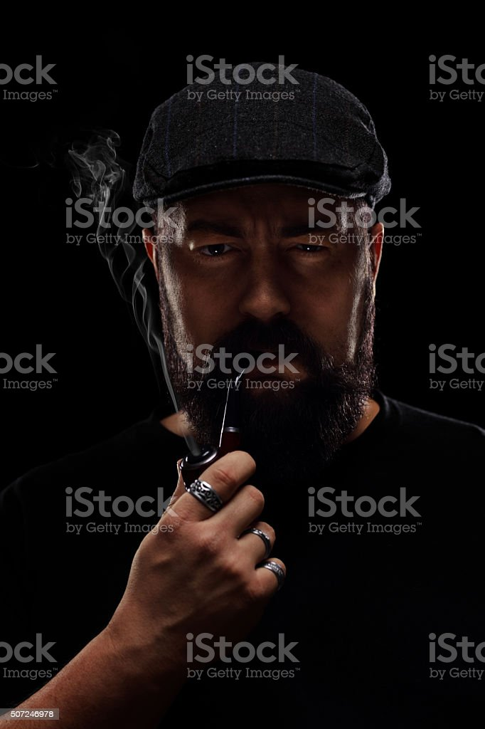 Man with a beard and a beret smoking a pipe stock photo
