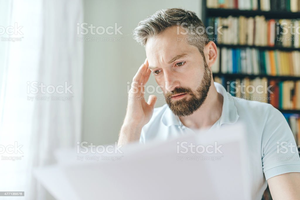 man with a beard looking over papers stock photo