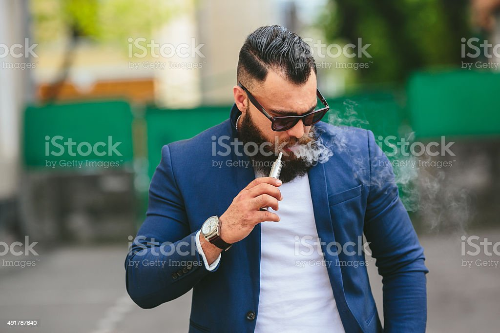 man with a beard smokes electronic cigarette stock photo