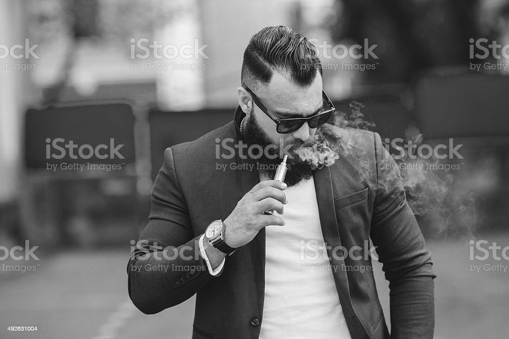 man with a beard smokes electronic cigarette stock photo