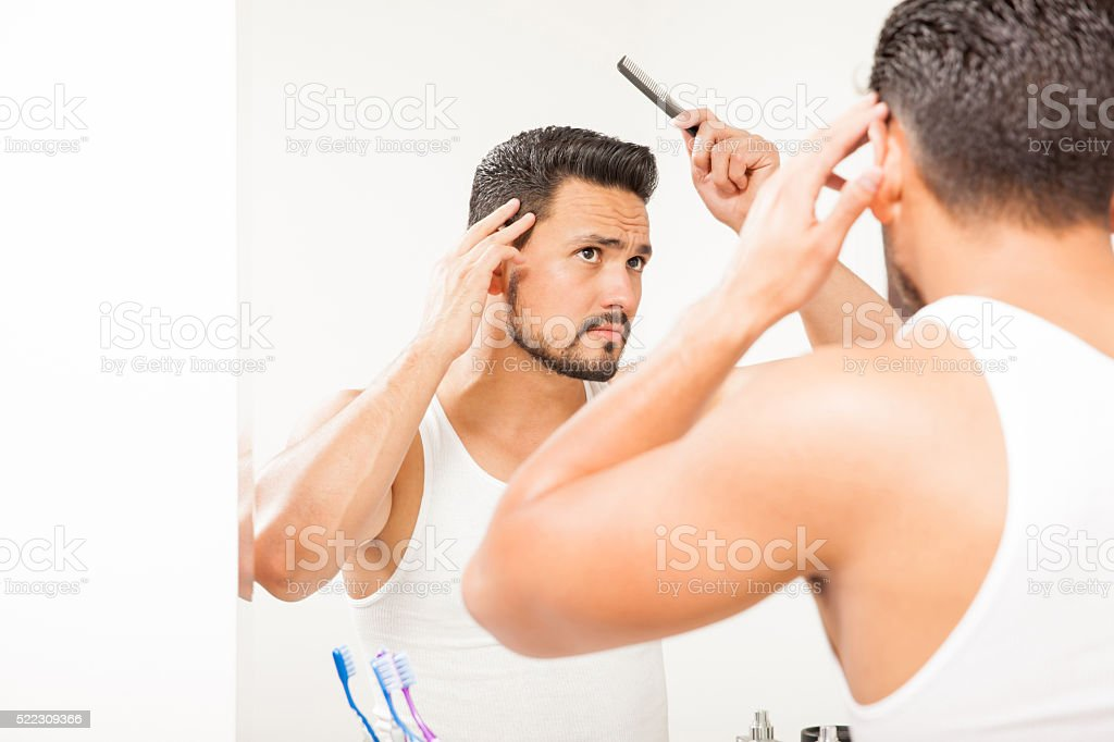 Man with a beard styling his hair stock photo
