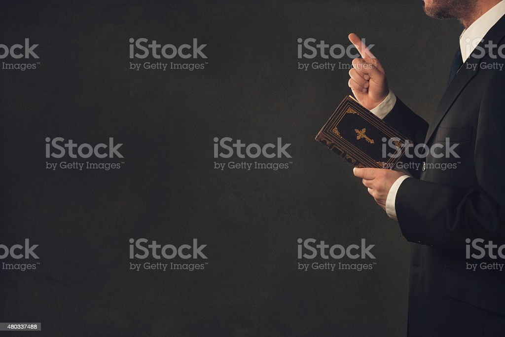 Man with a Bible and a wagging finger stock photo
