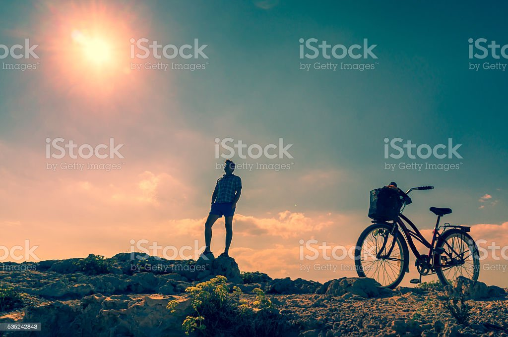 Man with a bicycle on a mountain road stock photo