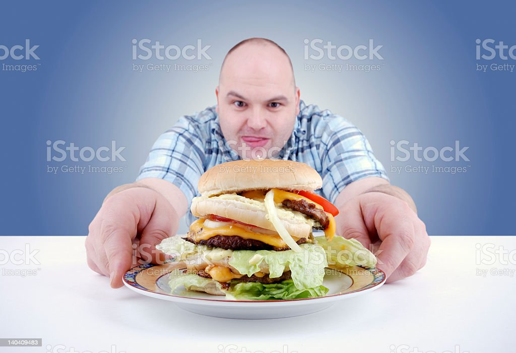 A man with a big greasy burger on a plate stock photo