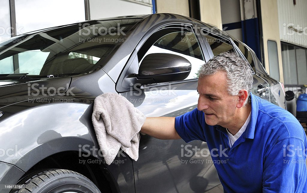 Man with a blue shirt wiping the driver's side of a grey car stock photo