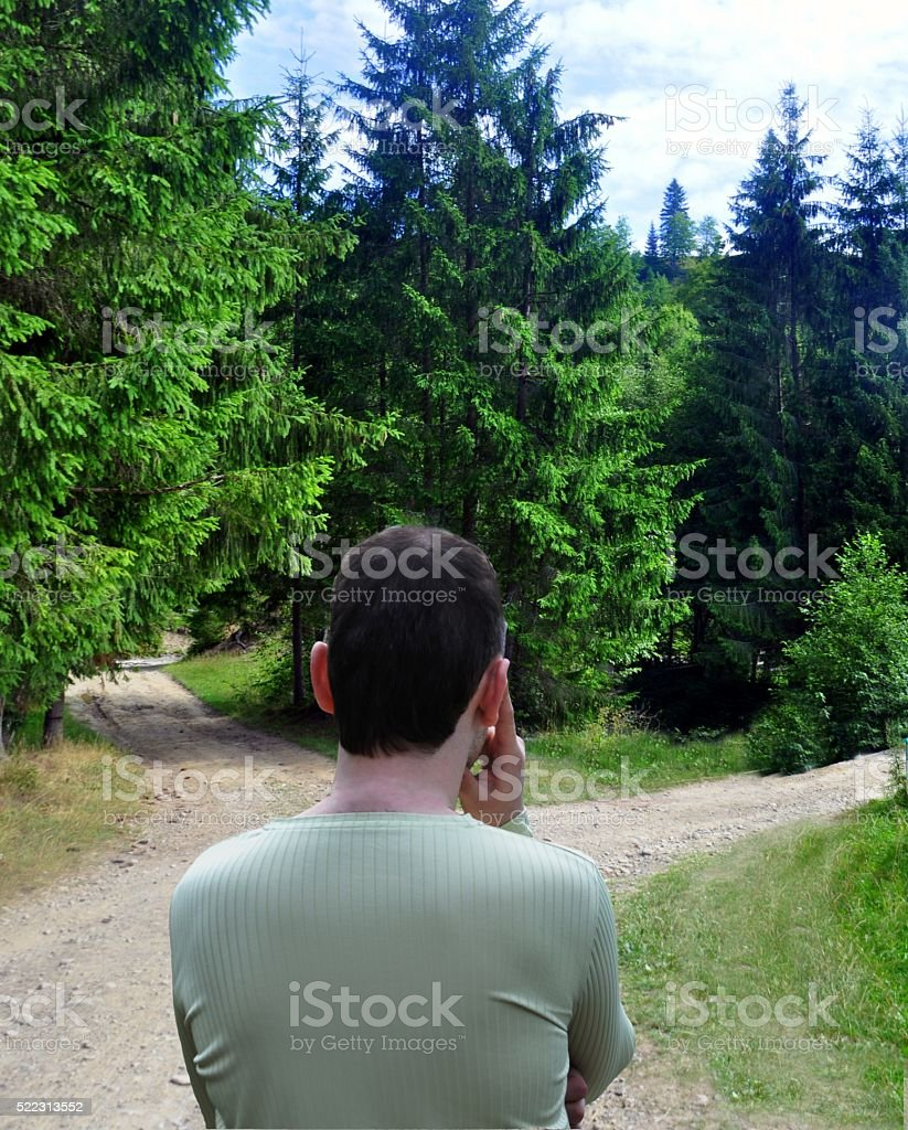 Man with a choice near the forked road stock photo