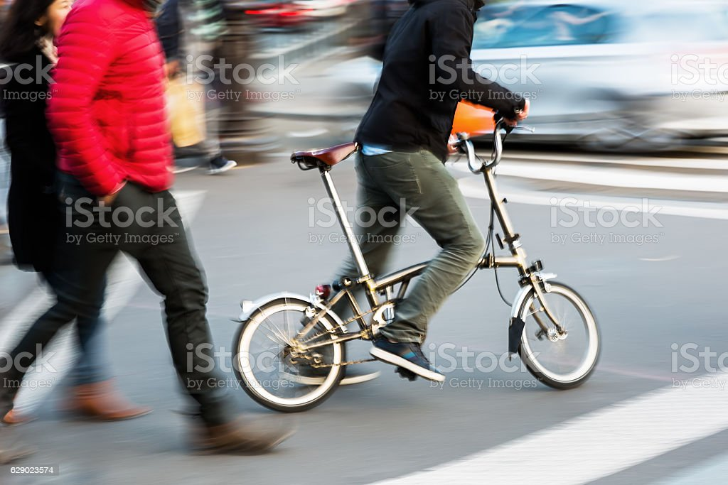 man with a city bicycle crossing a street stock photo