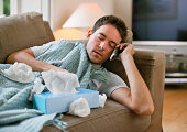 Man with a cold lying in sofa holding tissues while talking on cell phone