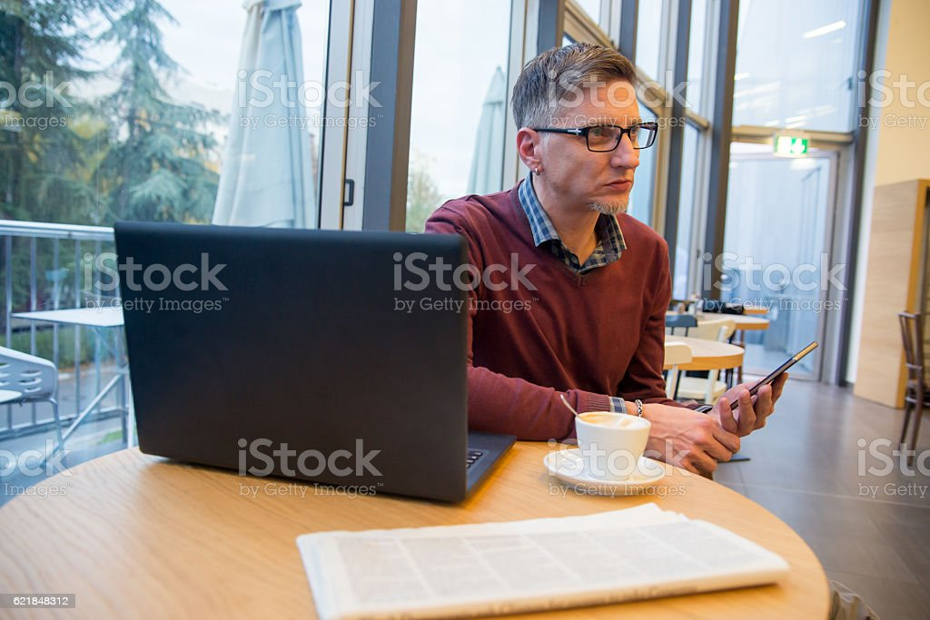 man with a cup of coffee holding smartphone stock photo