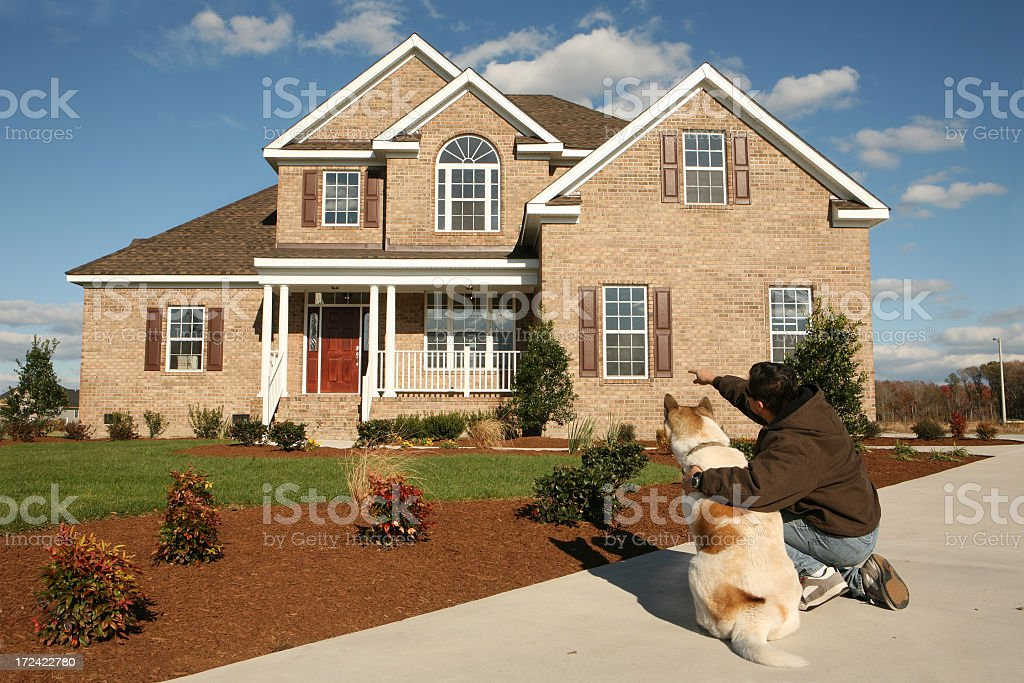 A man with a dog pointing at a house stock photo
