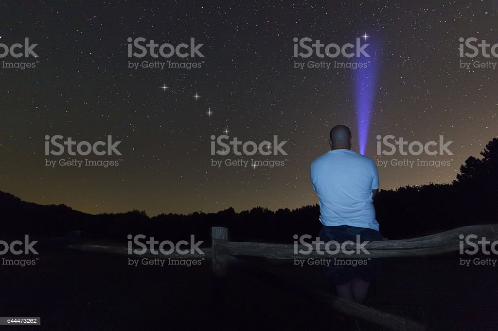 Man with a flashlight pointing to Polaris star. North star. stock photo