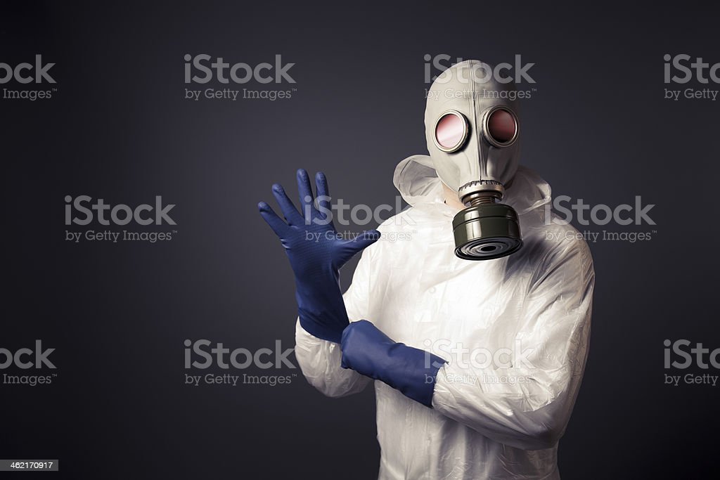 Man with a gas mask puting on his gloves stock photo