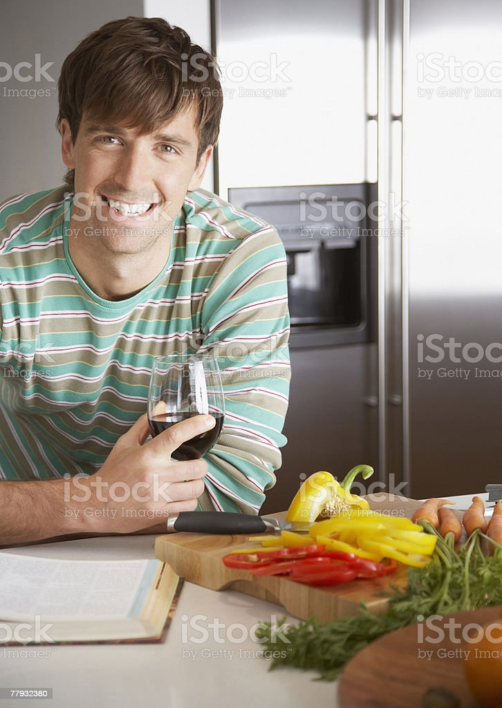Man with a glass of wine and chopped peppers beside him royalty-free stock photo