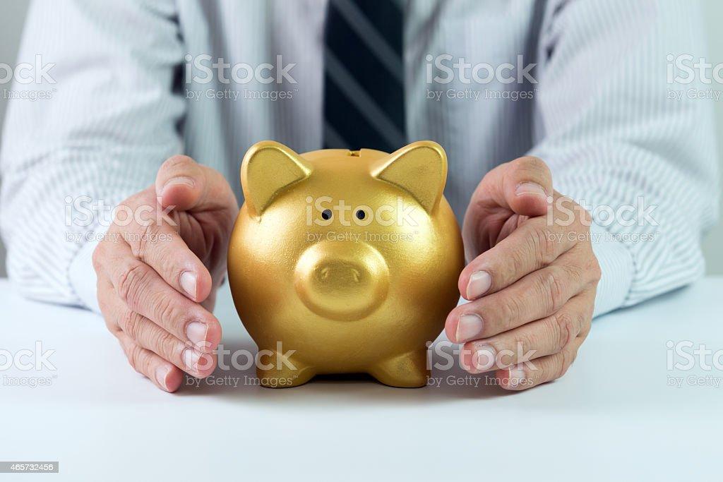 A man with a golden piggy bank stock photo