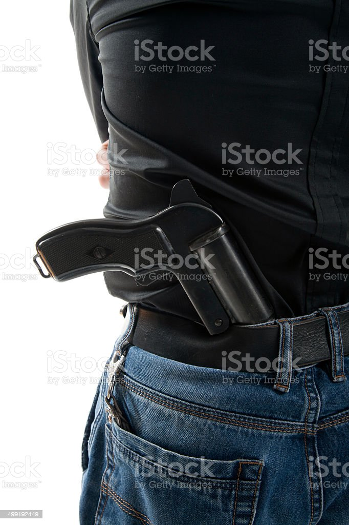 Man with a gun behind his back stock photo
