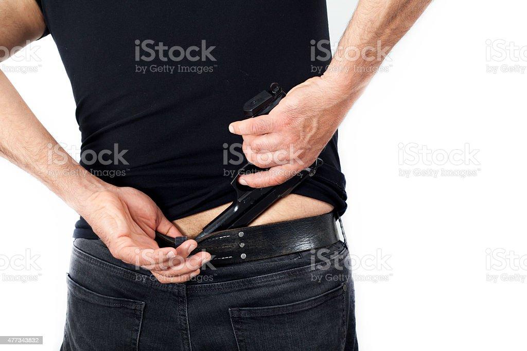 Man with a gun his pants stock photo