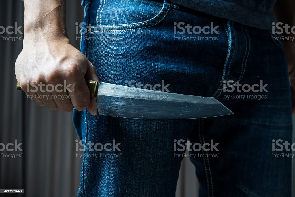 Man with a knife in a hand , in dark tone stock photo