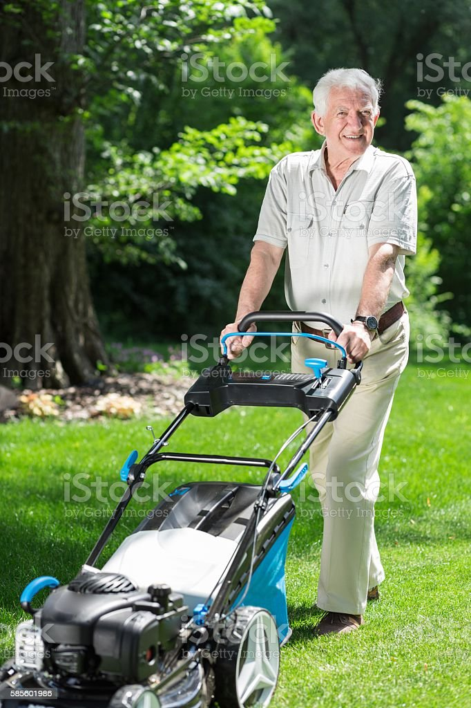 Man with a lawn mower stock photo
