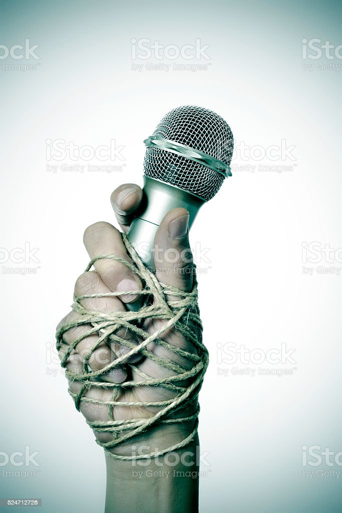 man with a microphone tied with rope stock photo