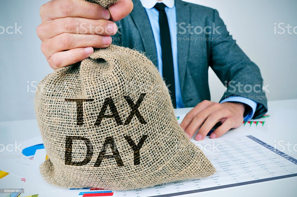 man with a money bag with the text tax day stock photo