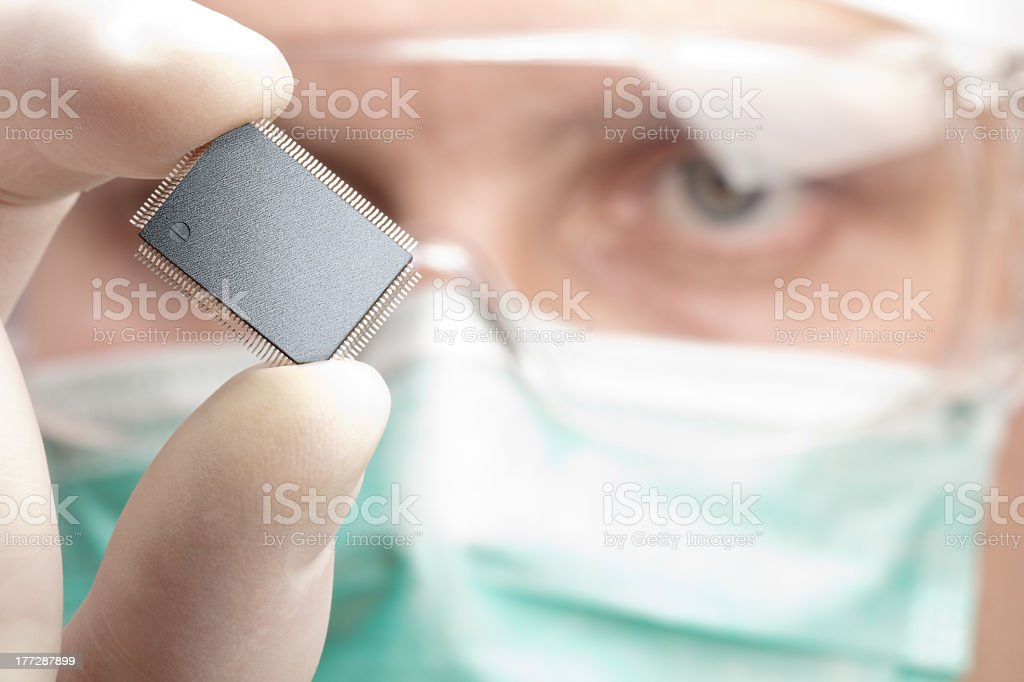 A man with a mouth mask examining a microchip stock photo