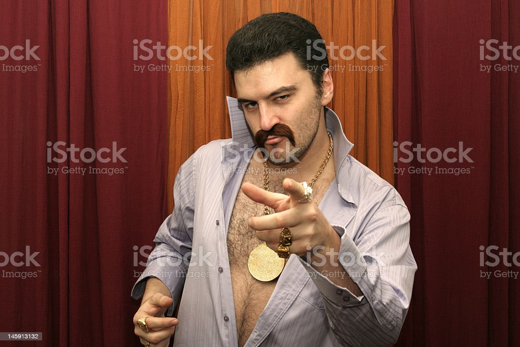 Man with a mustache and his shirt unbuttoned pointing royalty-free stock photo