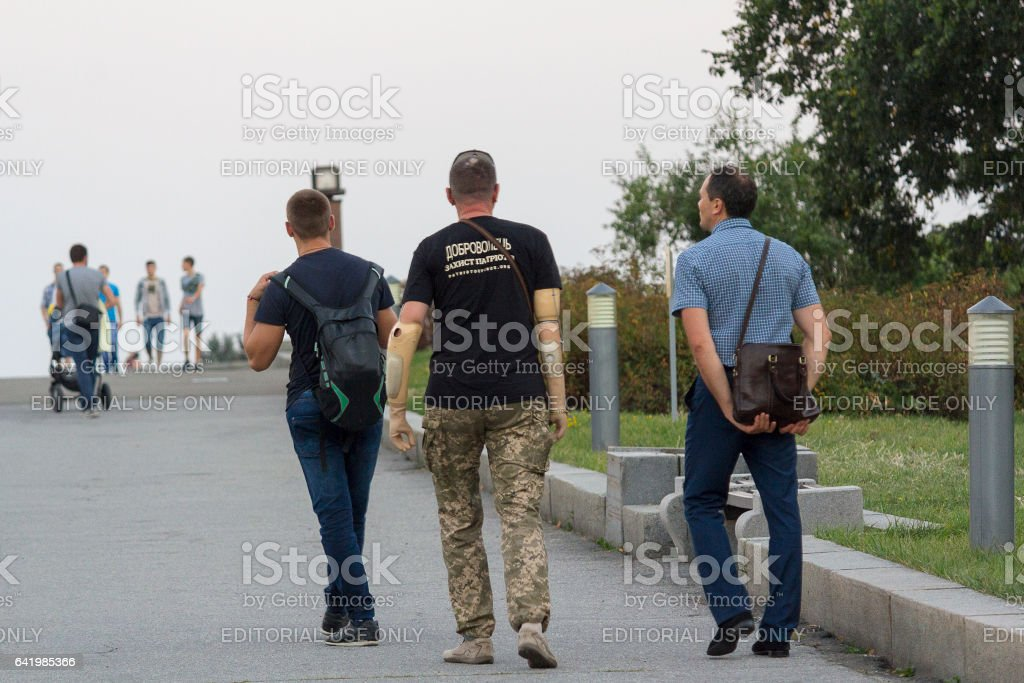 Man with a prosthetic hand walking in the park Glory stock photo