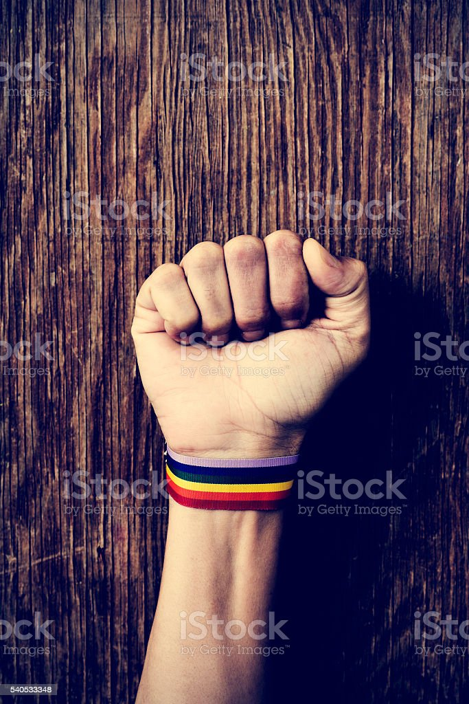 man with a rainbow-patterned band in his wrist stock photo