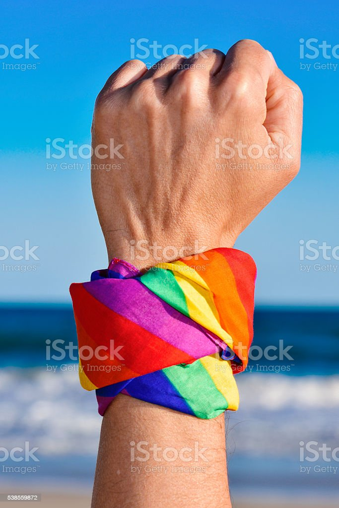 man with a rainbow-patterned kerchief in his wrist stock photo