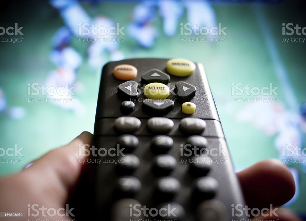 A man with a remote watching football on his tv stock photo