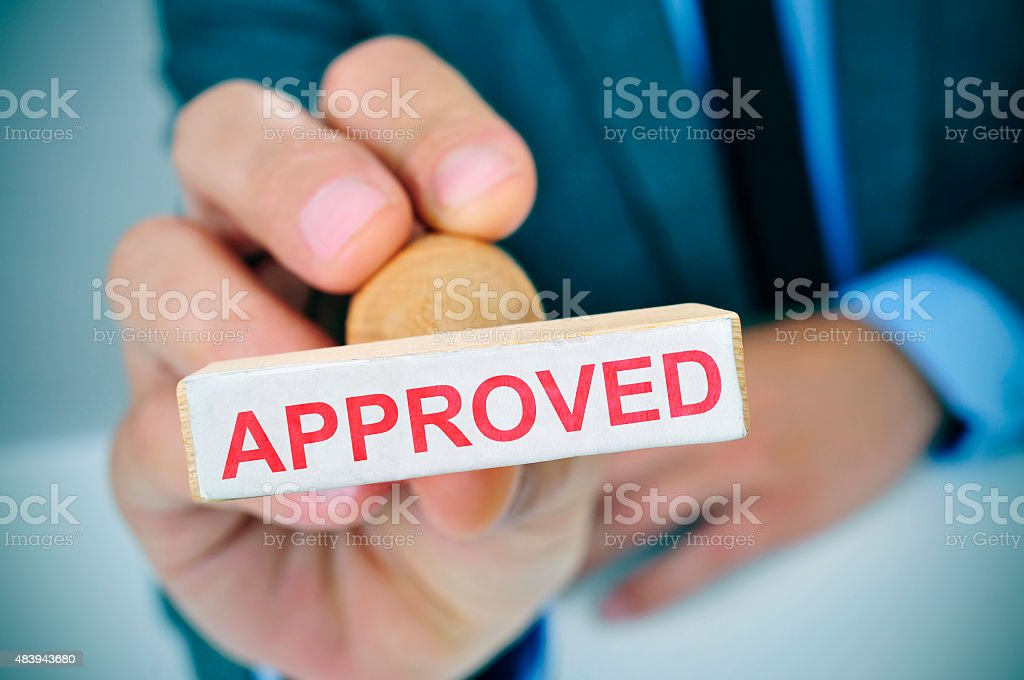 man with a rubber stamp with the word approved stock photo