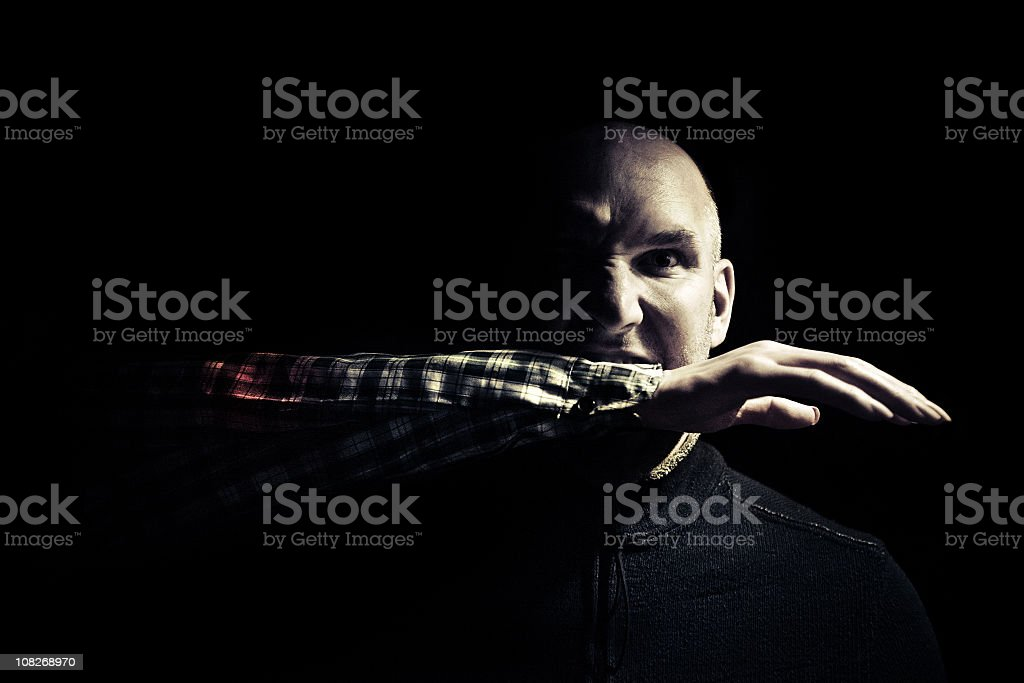man with a severed arm in his mouth stock photo