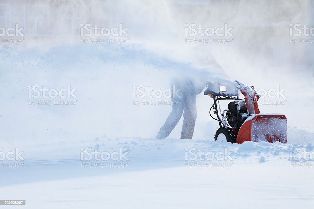 man with a snow blowing machine stock photo