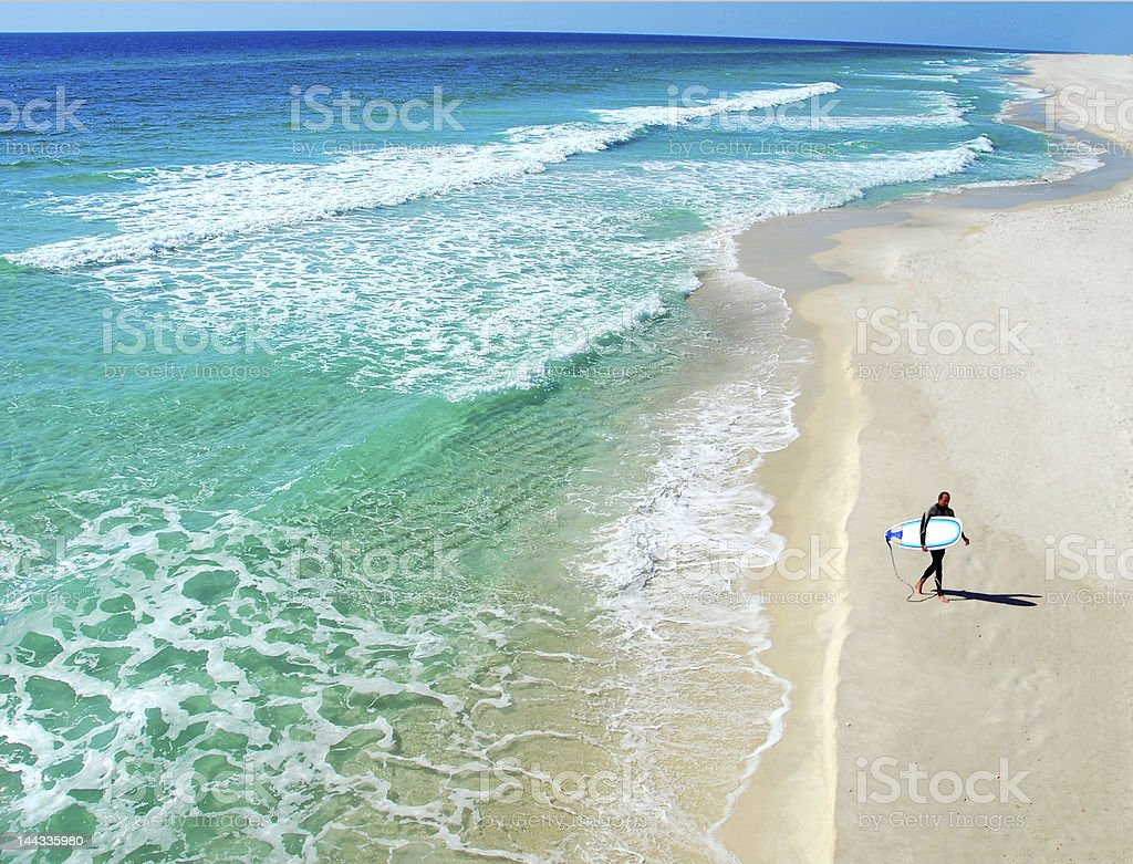 Man with a surfboard walking on the beach alone stock photo