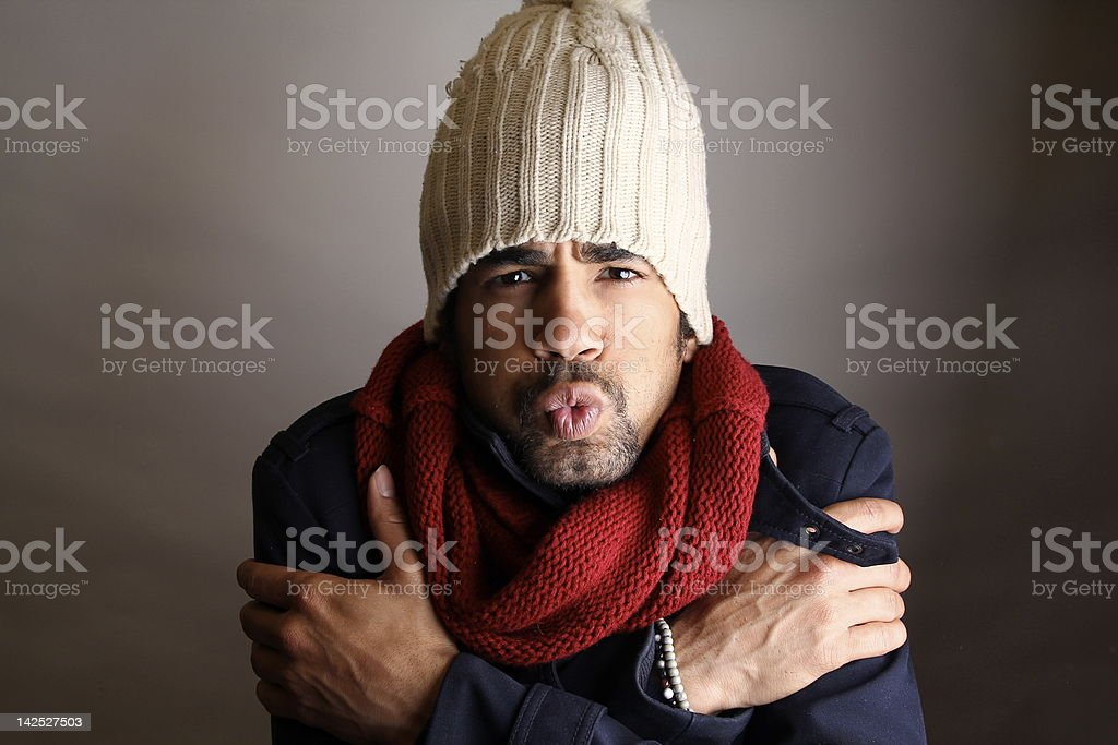 Man with a tan beanie and red scarf trying to warm up stock photo