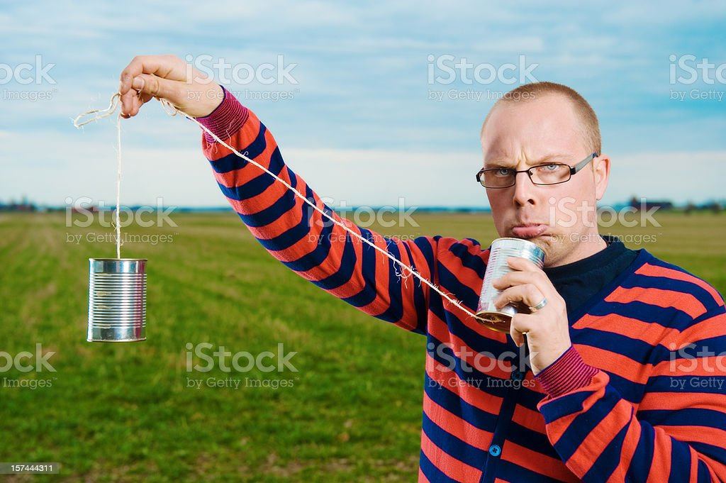 Man with a tin can phone stock photo