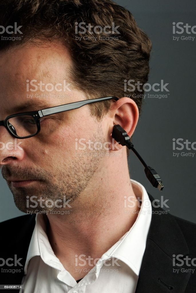 A man with a USB cable in his ear stock photo