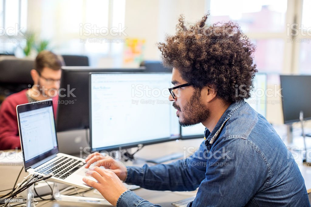 Man with afro hairstyle working at his desk stock photo