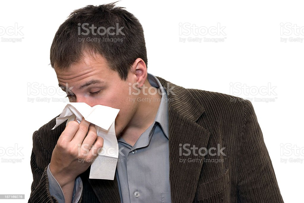 Man with allergies blowing nose on tissue stock photo