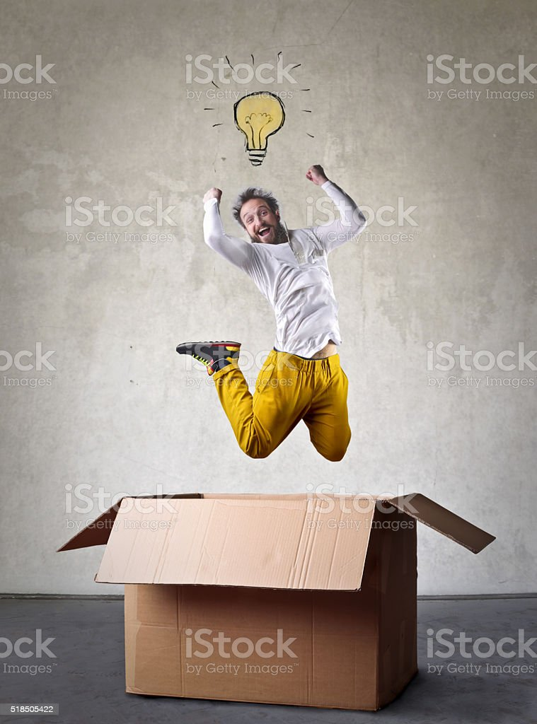 Man with an idea jumping out of a box stock photo