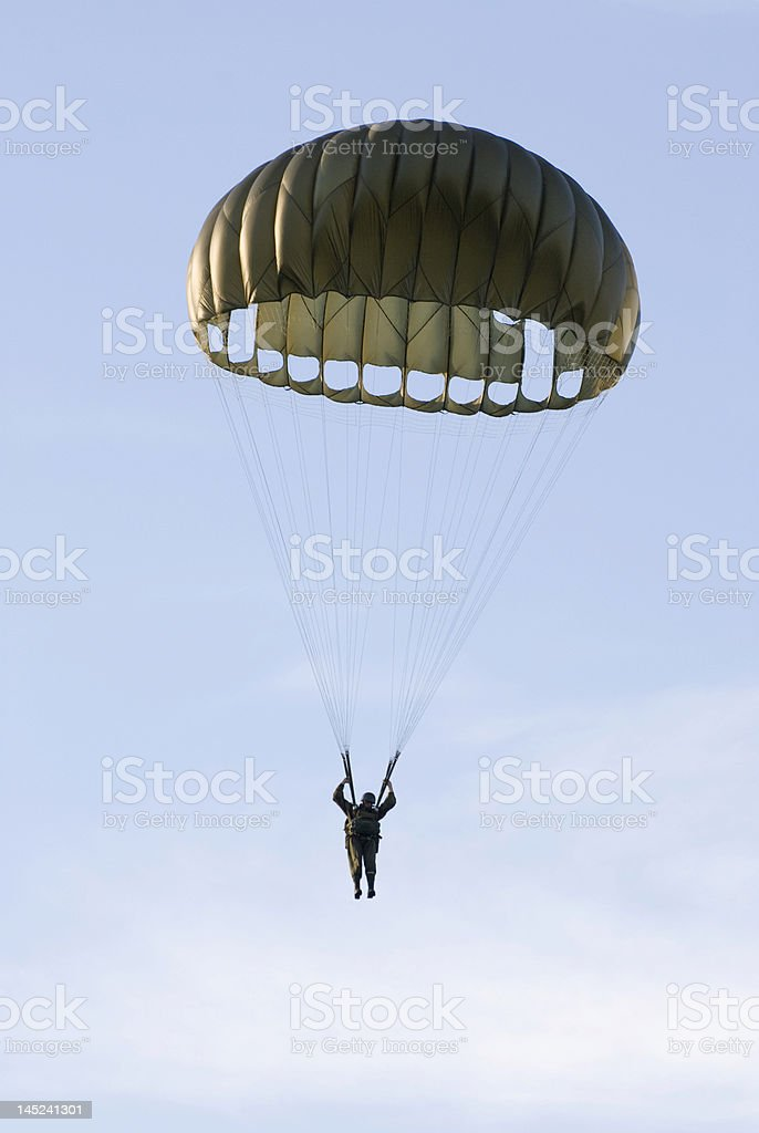 Man with an old-fashioned parachute coming down the sky stock photo