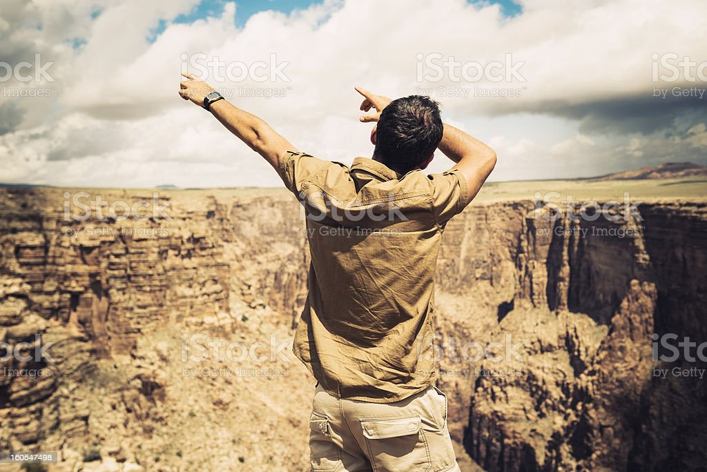 Man with arm raised gesturing on Grand Canyon - Usa royalty-free stock photo