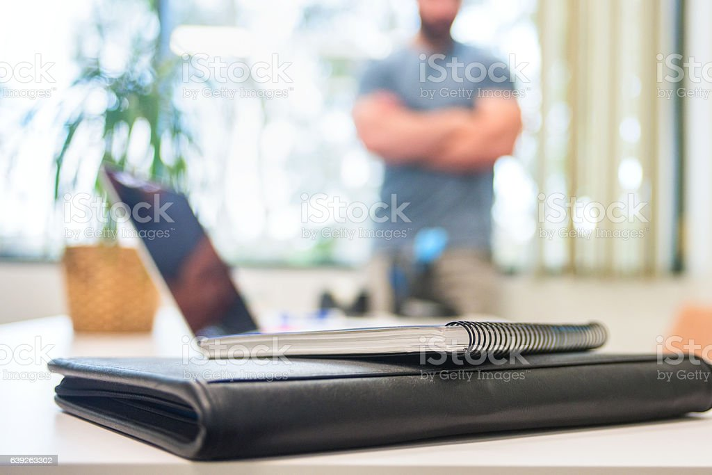 Man With Arms Crossed Leaning Against His Office Window stock photo