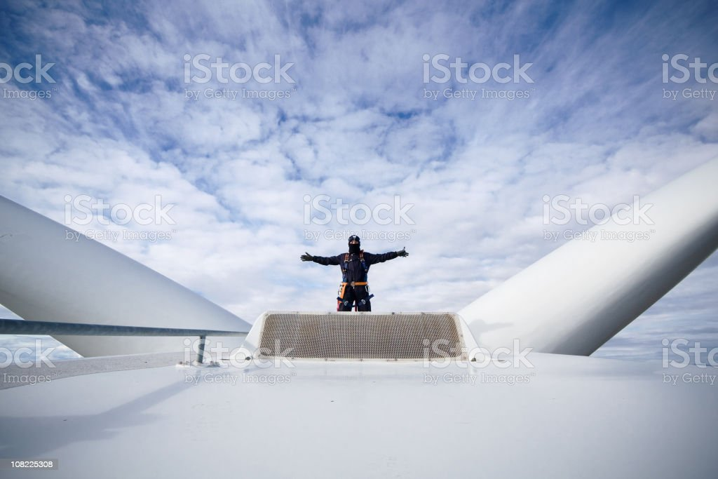 Man with arms open at work on a giant wind turbine stock photo