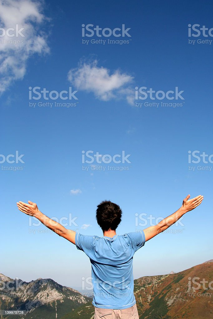 Man with arms outstretched in mountains royalty-free stock photo