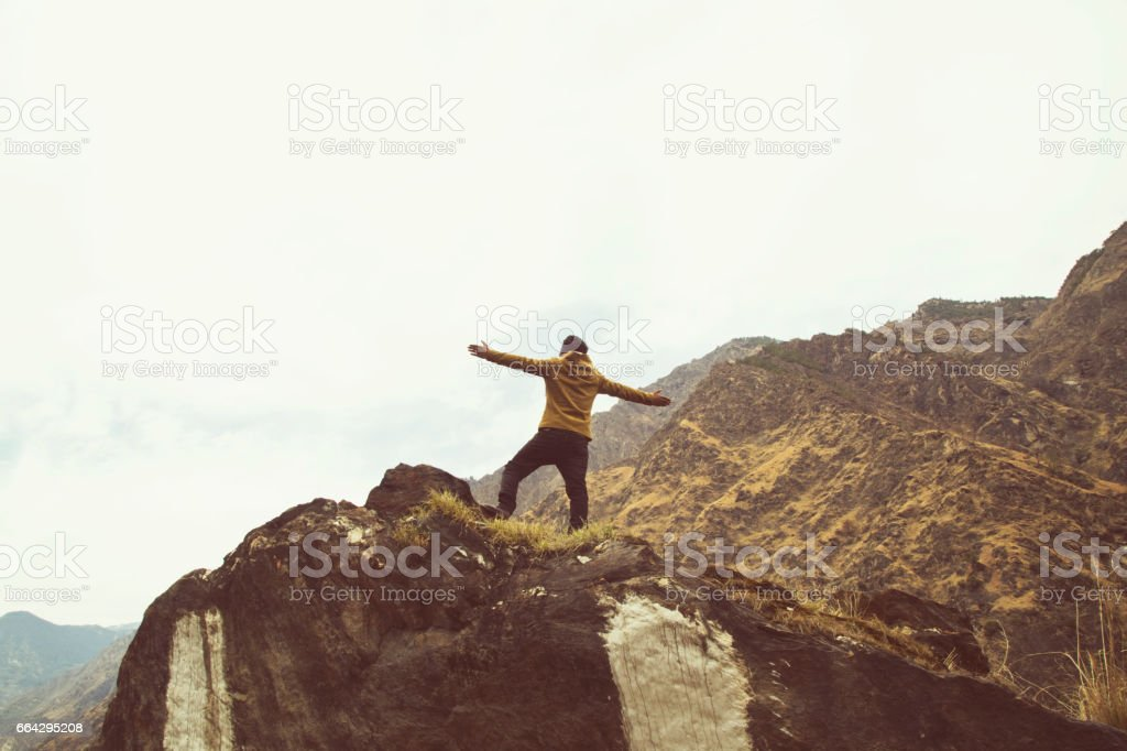 Man with arms outstretched on Himalayan mountain stock photo