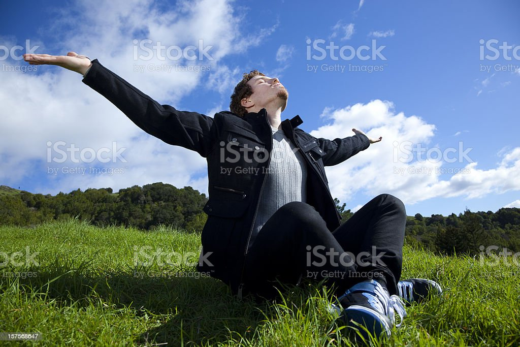 man with arms outstretched sitting on green grass royalty-free stock photo