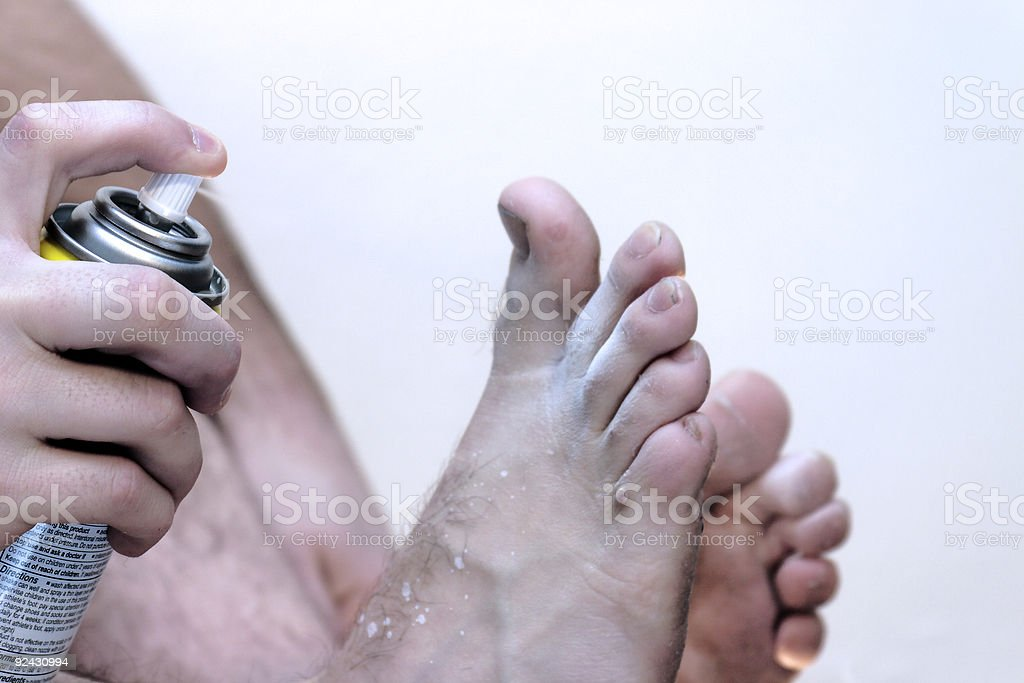 Man With Athlete's Foot Spraying Medication - Close-Up stock photo