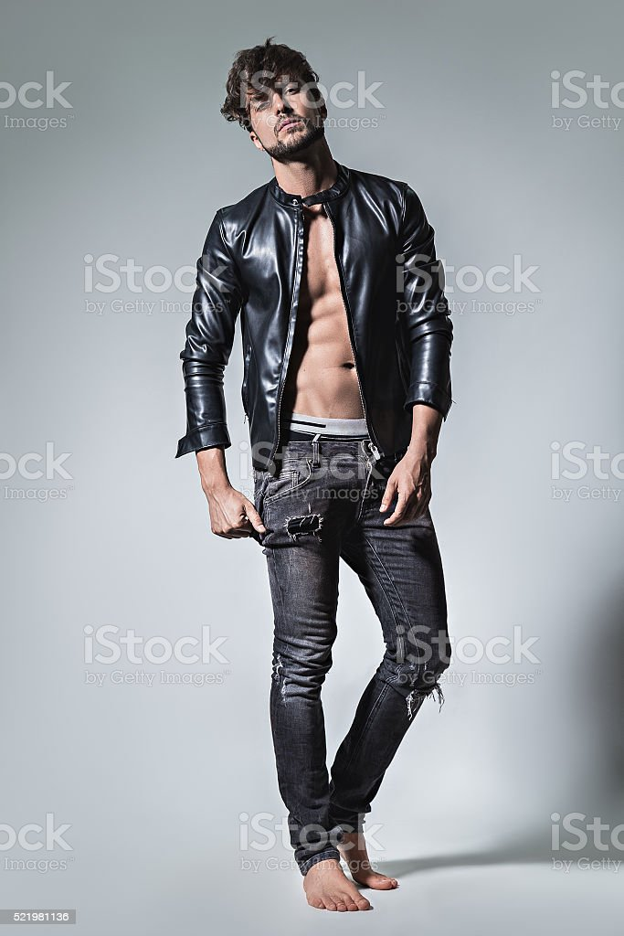 Man with attitude posing in leather jacket and jeans stock photo